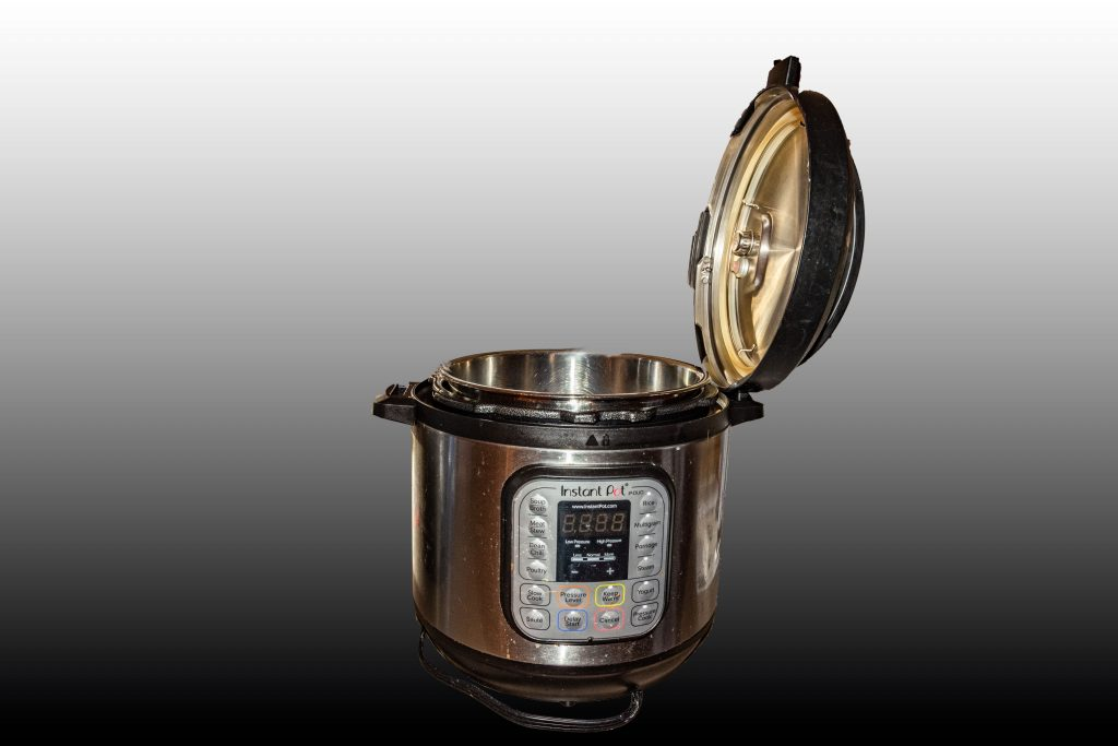 An 8-quart Instant Pot™ with its lid set in the pot's handle.