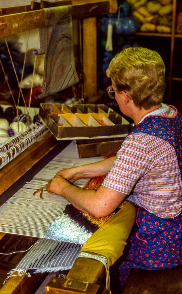 The weaver studies the cartoon and ties knots on the warp of the Montana Horses Tapestry.