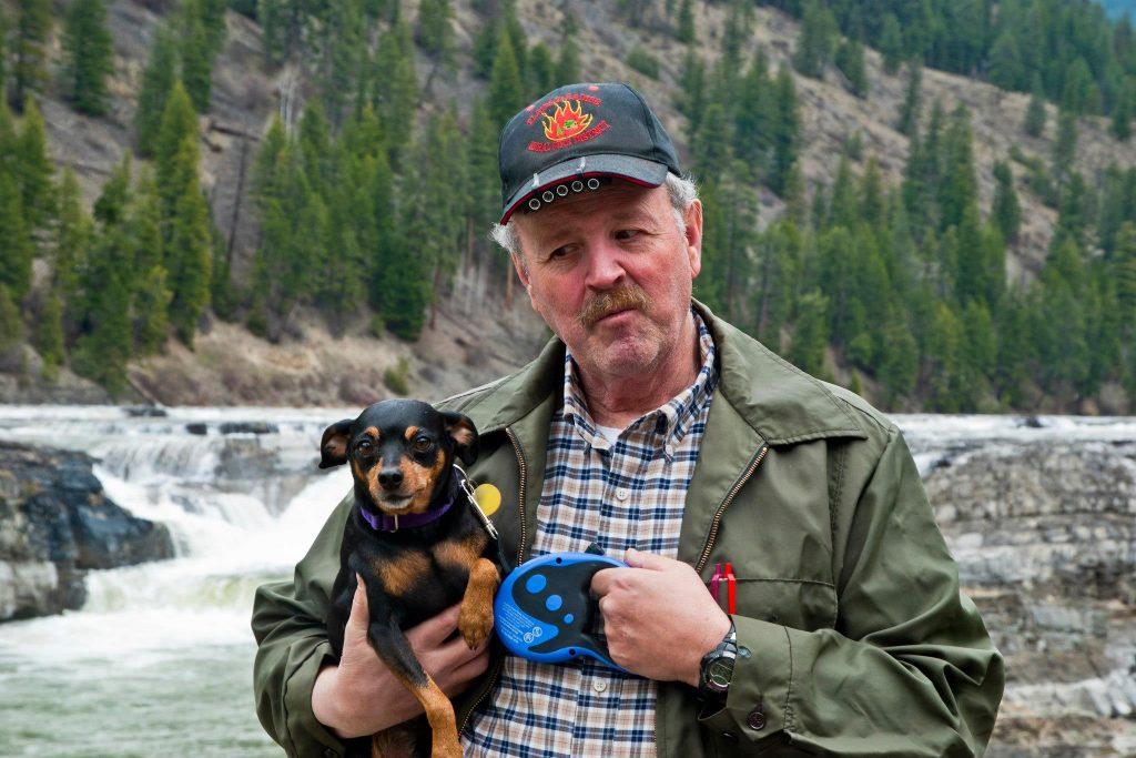 Man holding miniature pinscher (MinPin) at Kootenai Falls Montana