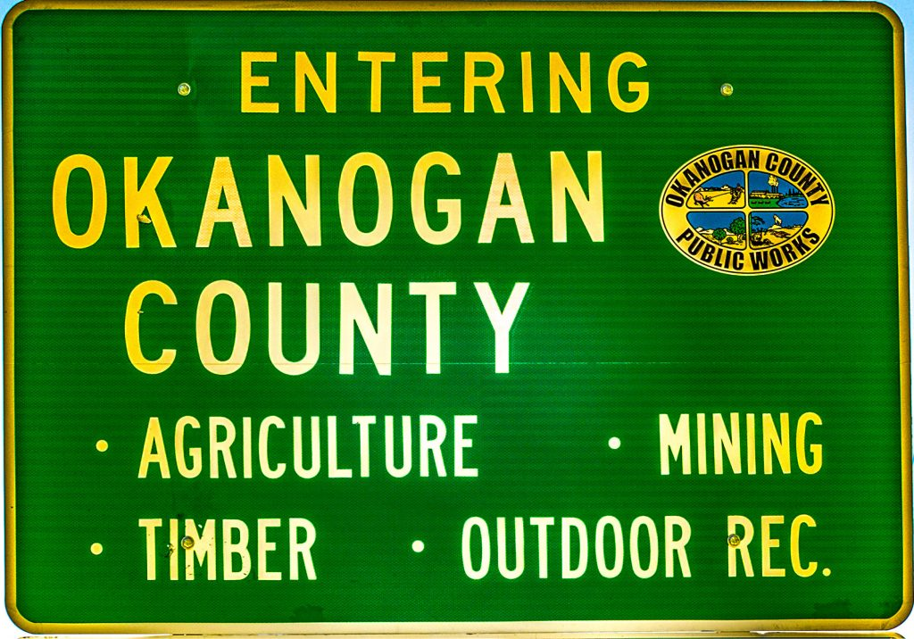 "The ""Welcome to Okanogan County"" sign on Washington Highway 20 west of Republic."