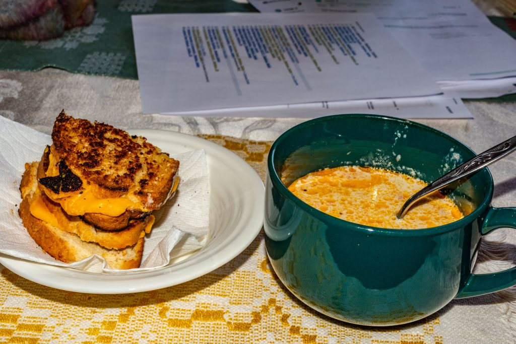A mug of Original 4B's homemade tomato soup served with a grilled cheese on homemade cracked wheat bread.